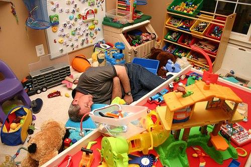 Мужчина спит среди разбросанных игрушек