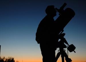 человек, наблюдающий за звёздами в телескоп
