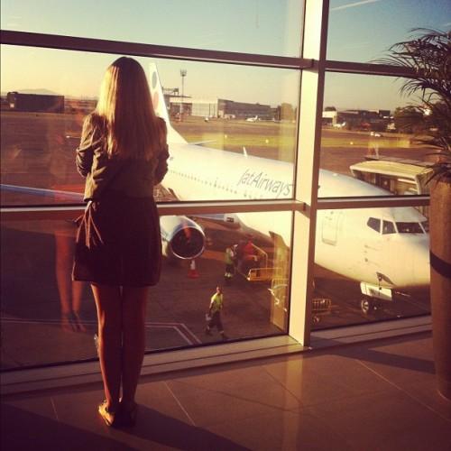 Как сэкономить на покупке авиабилетов, девушка смотрит в окно в аэропорту