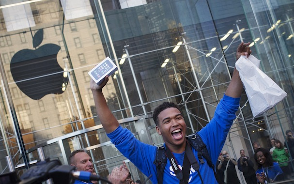 One of the first customers to purchase the Apple iPhone 5S celebrates after exiting the Apple Retail Store on Fifth Avenue in Manhattan
