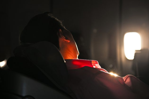 man sleeping in the seat of an aircraft in sunrise