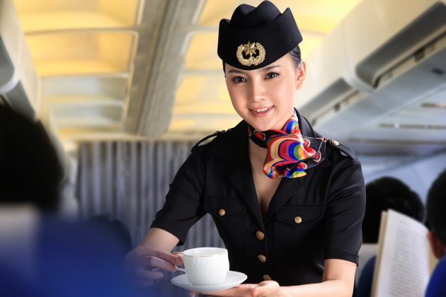 Flight attendant serving people on airplane