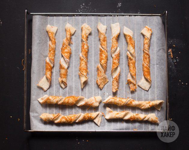 Разложите сырные палочки на пергаменте